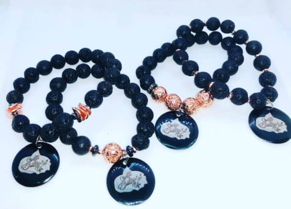 Four black lava bead bracelets with gold accents and an All butter'd up charm