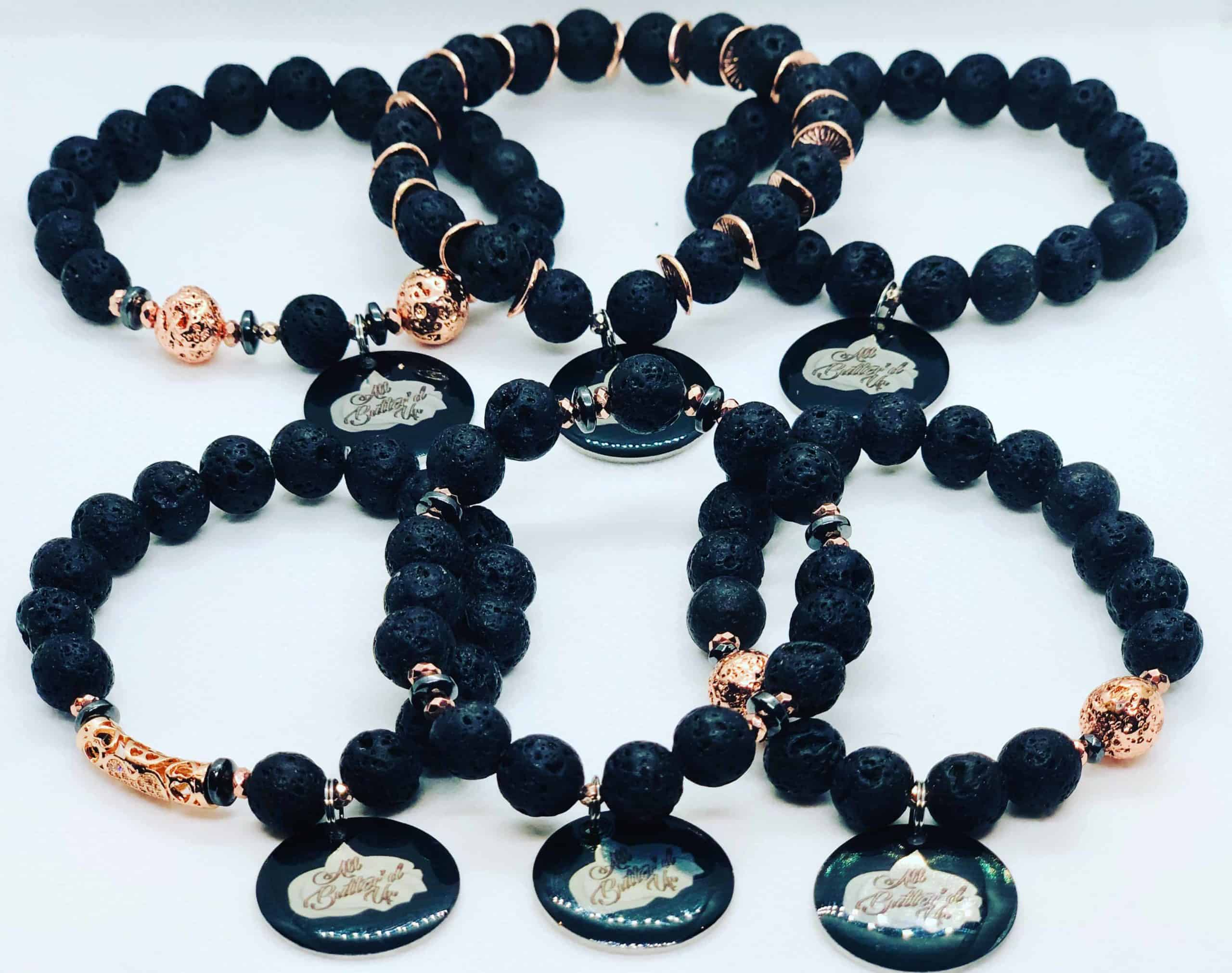 Six black lava bead bracelets with gold accents and an All butter'd up charm